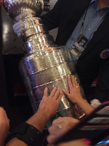 Author's hand touching the Stanley Cup